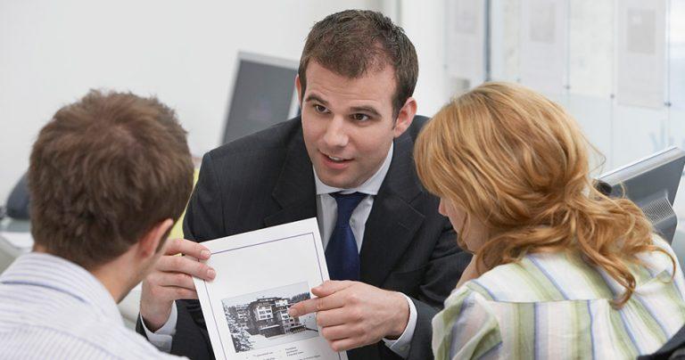 Un agent immobilier avec ses clients à l'agence