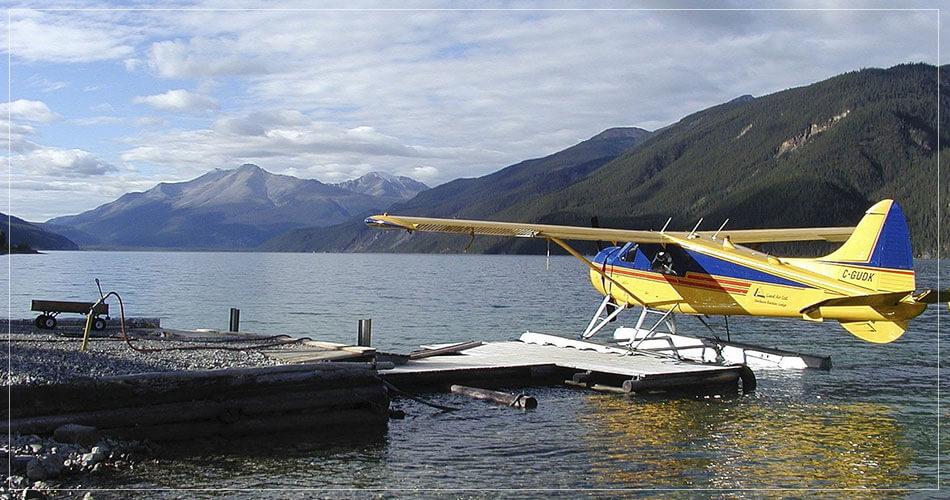Hydravion jaune sur un lac au milieu des montagnes canadiennes.