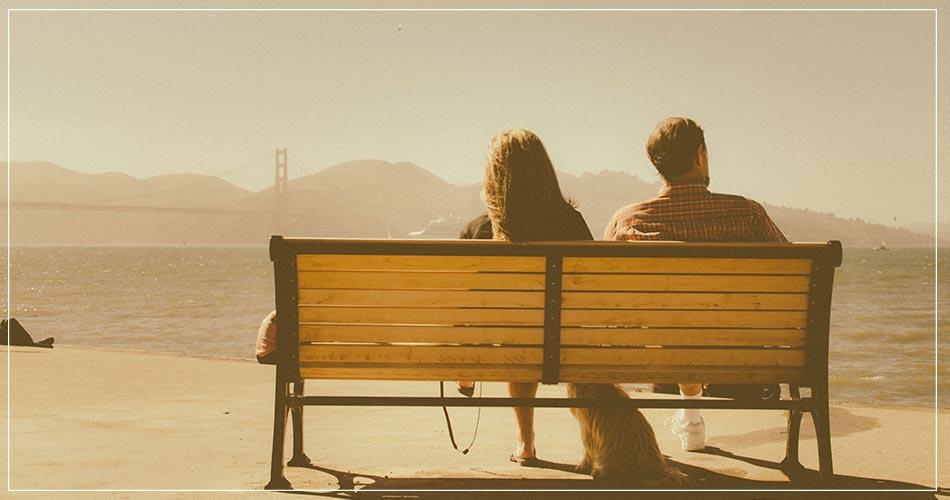 Couple d'expatriés sur un banc devant le Golden Gate à San Francisco