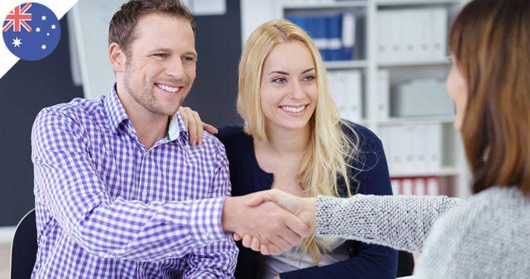 Couple souriant dans une agence lors d'un accord contractuel
