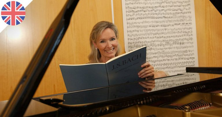 Elisabeth Sombart, pianiste française, souriante devant derrière son piano.