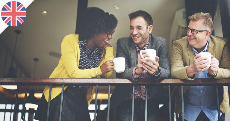 Groupe d'employés souriants en Angleterre à la pause café