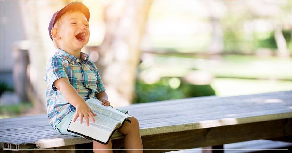 Jeune garçon riant avec un livre sur les genoux