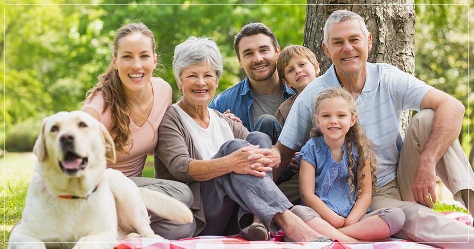 Une famille française à l'extérieur sous un arbre avec un chien