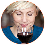 Jeune femme blonde qui savoure un verre de vin rouge