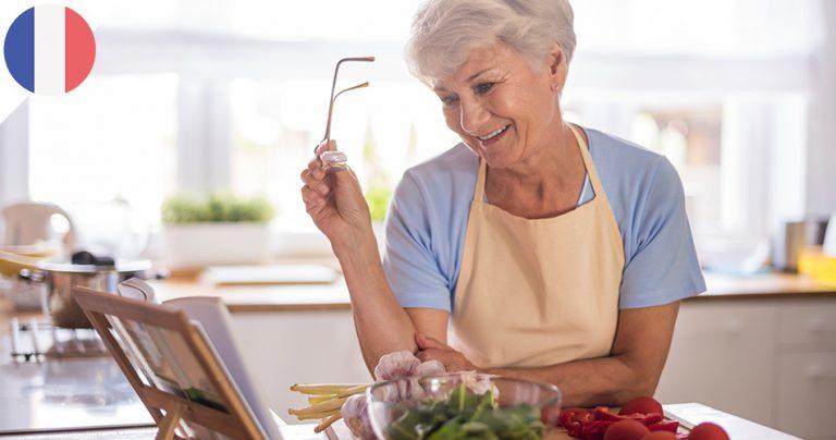 Charmante femme sénior avec son livre de recettes dans sa cuisine