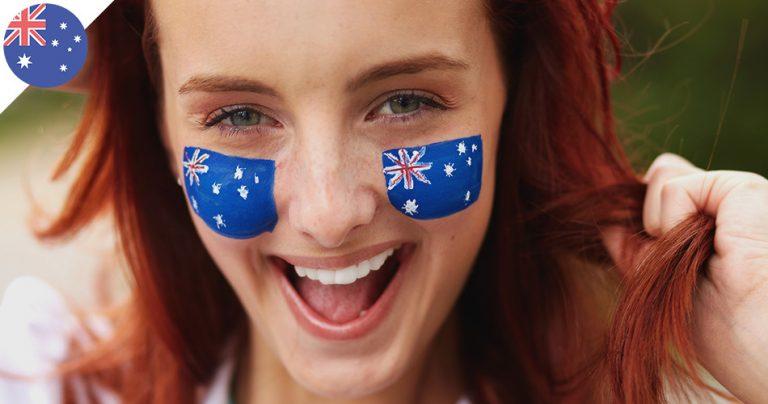 Jeune femme souriante avec le drapeau australien peint sur ses joues