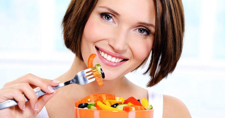 Jeune femme souriante qui mange sain après une séance de sport