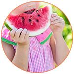 Une fillette qui déguste une tranche de pastèque
