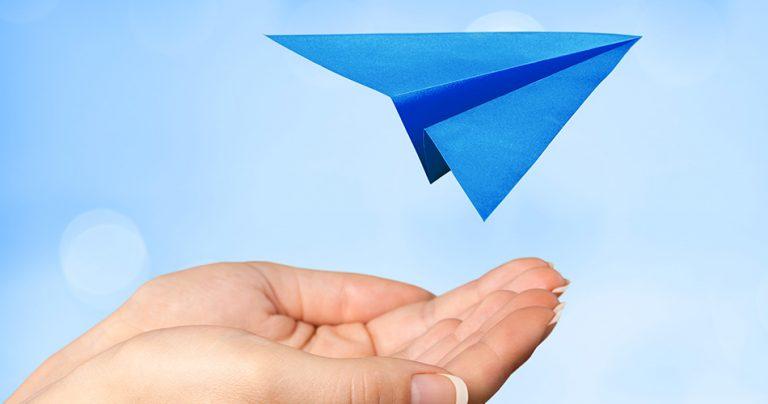 Illustration avec une main et un avion en papier bleu