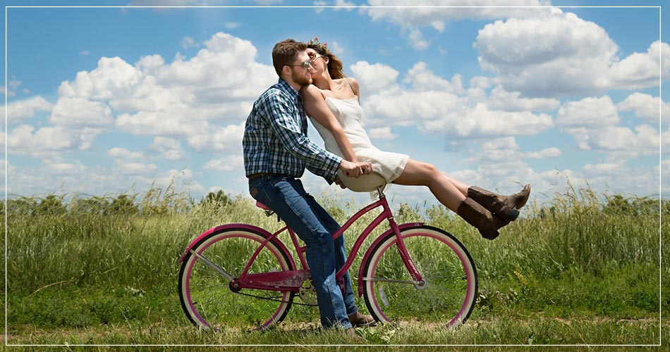 Jeune couple à bicyclette au milieu des champs