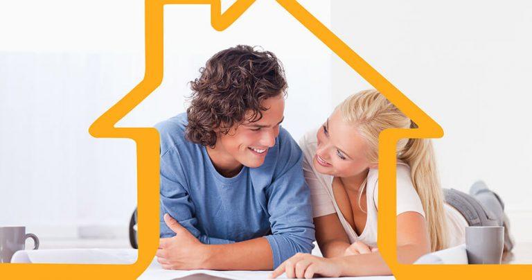 Jeune couple souriant allongé au sol lors d'une opération immobilière
