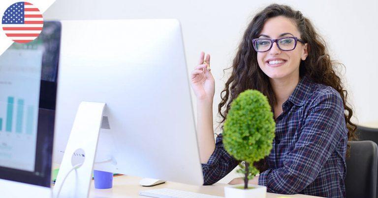 Jeune femme à lunettes souriante devant son ordinateur