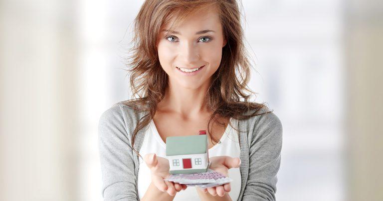 Jeune femme souriante avec une maison miniature dans les mains