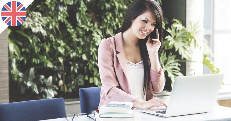 Jeune femme souriante en recherche d'emploi au téléphone en Angleterre
