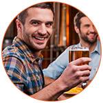 Jeune expatrié souriant buvant une bière avec ses amis