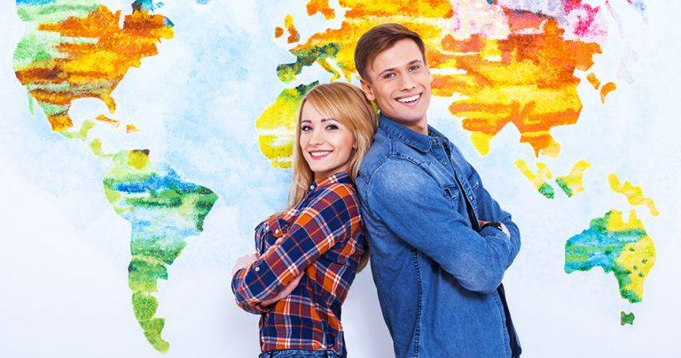 2 jeunes étudiants souriants avec une mappemonde en arrière plan