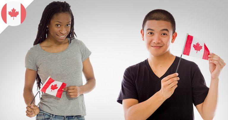 2 jeunes expatriés souriants présentent le drapeau canadien dans leurs mains