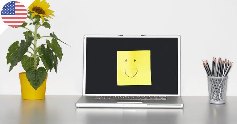Ordinateur portable avec un smiley sur un post-it jaune collé sur l'écran éteint