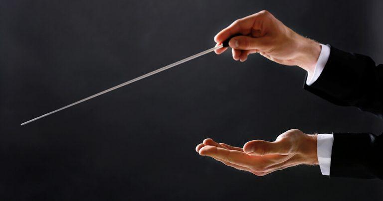 Les mains et la baguette d'un Chef d'Orchestre sur fond noir