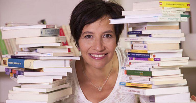 Nathalie Le Breton souriante entre 2 piles de livres