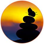 Ombre d'un papillon posé sur des pierres zen avec un ciel orangé