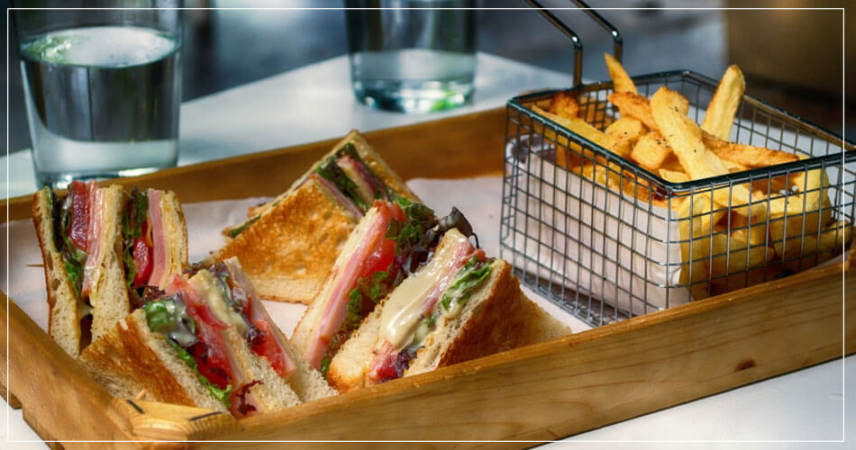 Plateau avec sandwiches, frites et verre d'eau