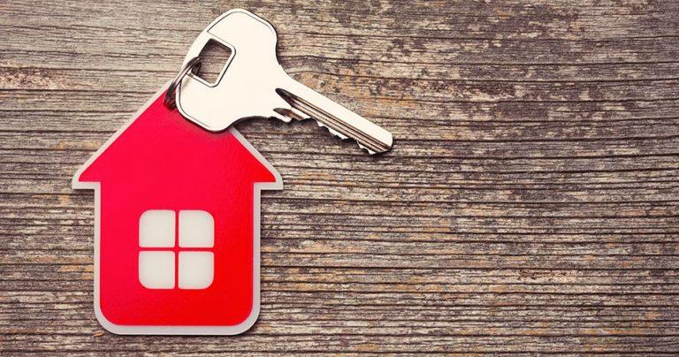 Porte clés en forme de maison rouge sur une planche en bois