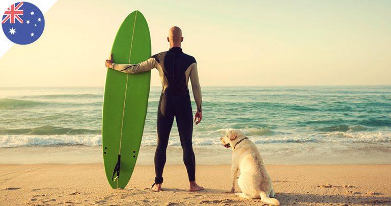 Surfeur australien de dos avec son chien sur la plage