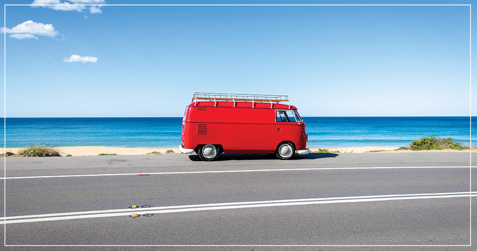 Van rouge stationné au bord de la plage