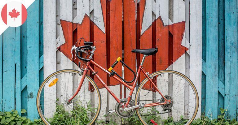 Vélo rouge posé contre un portail avec la feuille d'érable du Canada