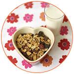 Verre de lait avec un bol de céréales en forme de coeur sur une nappe à fleurs rouges