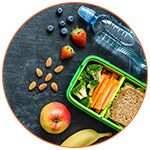 Snack léger pour un voyage : fruits secs, eau, sandwich, pomme, banane