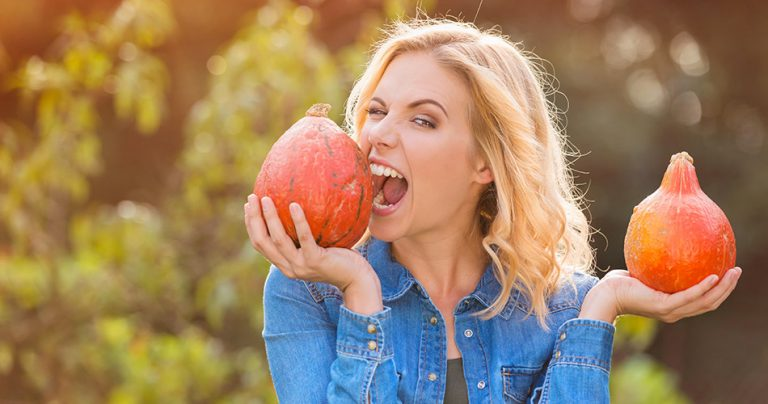Jeune femme souriante avec 2 citrouilles qui pratique le wwoofing
