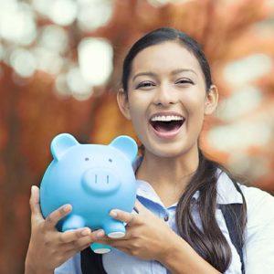 Jeune femme souriante avec une tirelire cochon